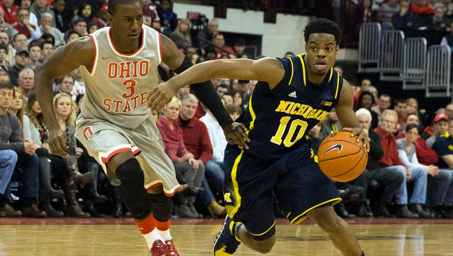 Michigan Wolverines guard Derrick Walton Jr.  drives around Ohio State Buckeyes guard Shannon Scott at Schottenstein Center.