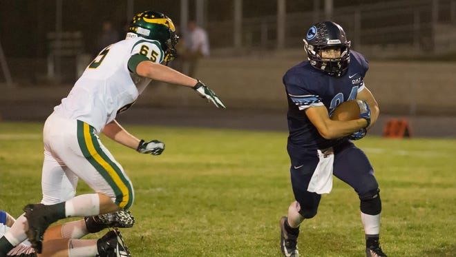 CVC's Macintyre Garbani (24) rushes past Kingsburg's Austin Crawford (65)