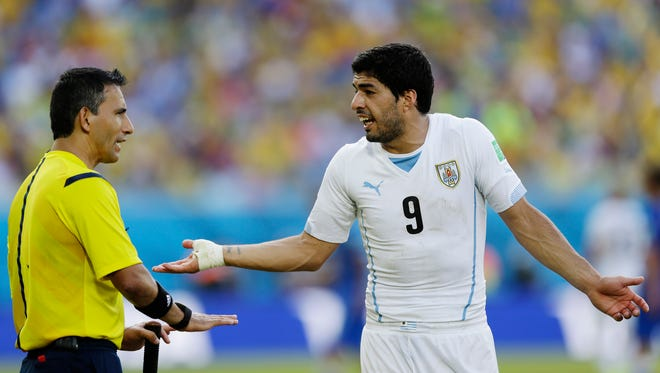 Uruguay's Luis Suarez argues with referee Marco Rodriguez from Mexico during the group D World Cup soccer match between Italy and Uruguay at the Arena das Dunas in Natal, Brazil, Tuesday, June 24, 2014. (AP Photo/Ricardo Mazalan)