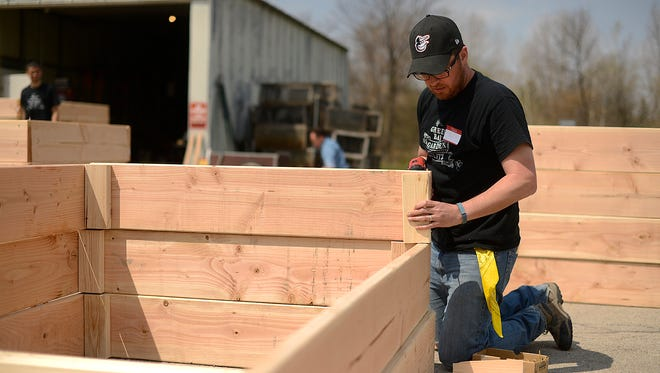 Paul DesJardins, volunteer, works on assembling a raised bed garden box outside the Brown County UW-Extension office in Belleuve on Saturday, May 2, 2015. This weekend is the 2nd annual Green Bay Garden Blitz, a three-day event in which over 100 volunteers are building and installing 130 raised bed garden boxes.