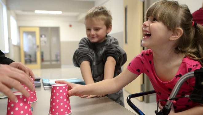 Ahlina Nicholson, 5, right, and Carson Dixson, 7, play games while they wait for a dental checkup Friday during the Give Kids A Smile Health Fair in the Shasta College Health Science Building in downtown Redding.