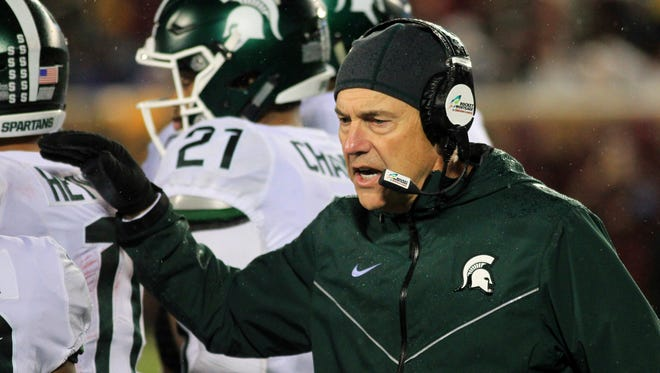 Michigan State coach Mark Dantonio congratulates players after a touchdown against Minnesota in the first quarter on Saturday, Oct. 14, 2017, in Minneapolis.