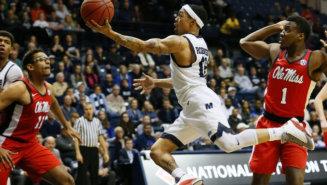 Monmouth Hawks guard Justin Robinson (12) drive to the basket against Mississippi Rebels guard Deandre Burnett (1)  during first round of NIT at Ocean First Bank Center, West Long Branch,NJ. Tuesday, March 14, 2017.  Noah K. Murray-Correspondent/Asbury Park Press ASB 0315 Monmouth Basketball