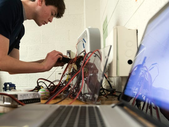 Spencer McDonald works on the electronic components of a machine designed to extract water from Mars' surface on Tuesday, Jan. 30, 2018. Hatcher is part of a team of University of Tennessee students who are finalists in the RASC-AL Special Edition: Mars Ice Challenge.