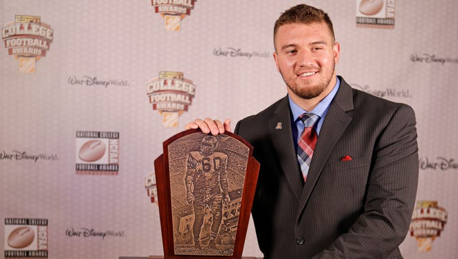Arizona's Scooby Wright III stands with his trophy after being awarded the Chuck Bednarik Award as the defensive player of the year at the College Football Awards on Dec. 11, 2014, in Lake Buena Vista, Fla.