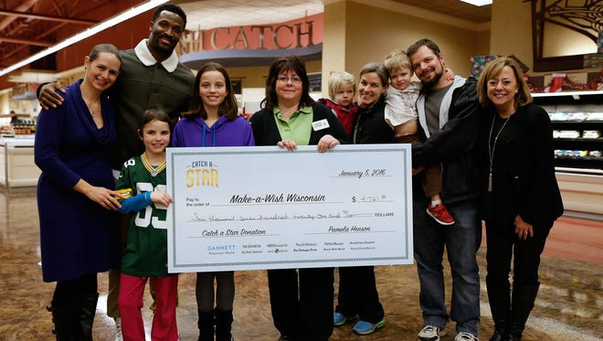 Eight-year-old Maggie Hendrick, of Appleton, (wearing Packers jersey) created a holiday greeting card along with Green Bay Packers wide receiver James Jones (back left) to raise money for the Children's Hospital of Wisconsin and Make-A-Wish. That check for $4721.50 was presented on Tuesday, Jan. 5, 2016 at the Copps off of Lime Kiln road, one of the locations the card was sold.