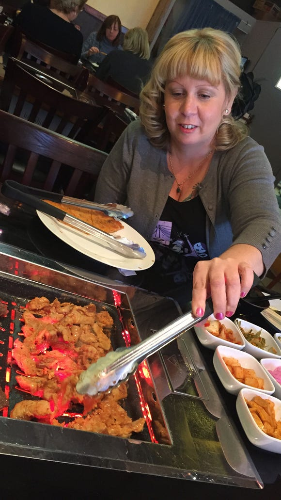 Christina Jordan of Melbourne Beach grills spicy chicken bulgogi on the tabletop grill at Mangetsu in Melbourne.