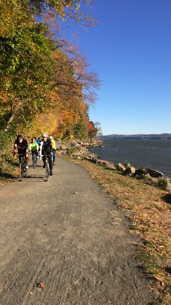 A group of cyclists ride along the bike path between the Palisades and the Hudson River north of Nyack, N.Y.