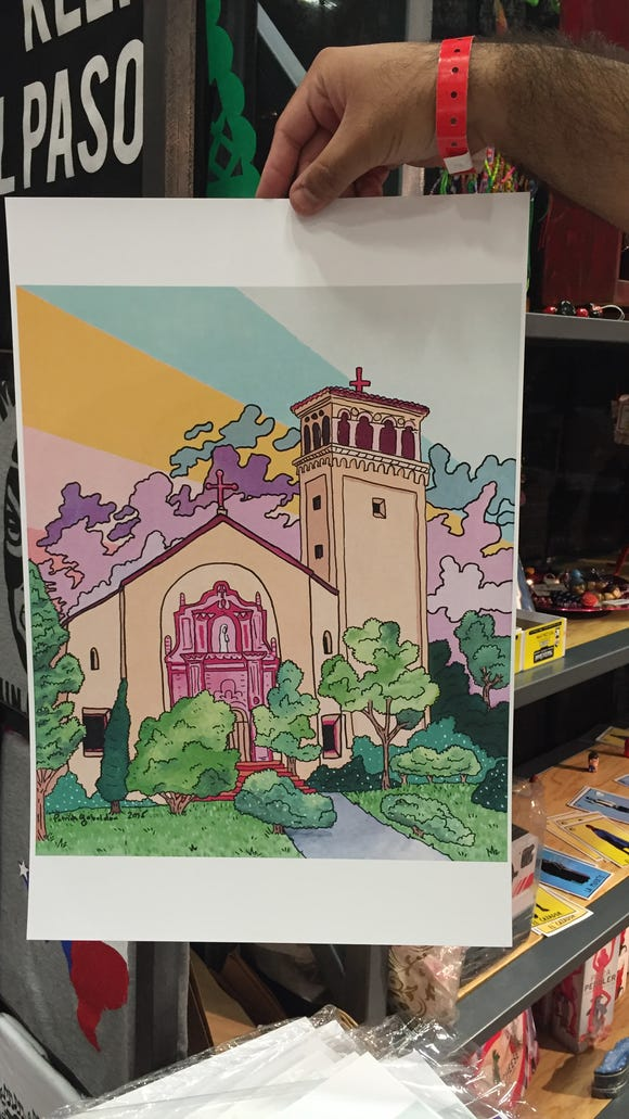 A print is seen from artist Patrick Gabaldón at the Manchot booth at the Junior League of El Paso's Christmas Fair.