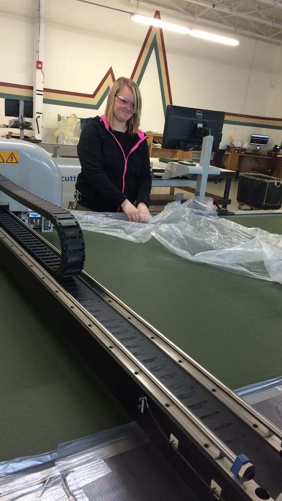 A First State Manufacturing employee cutting seats.