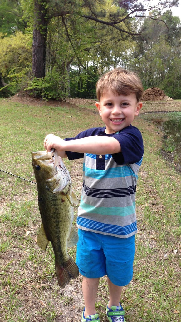 Grant Perrone, 5, holds a bass that he hooked and landed
