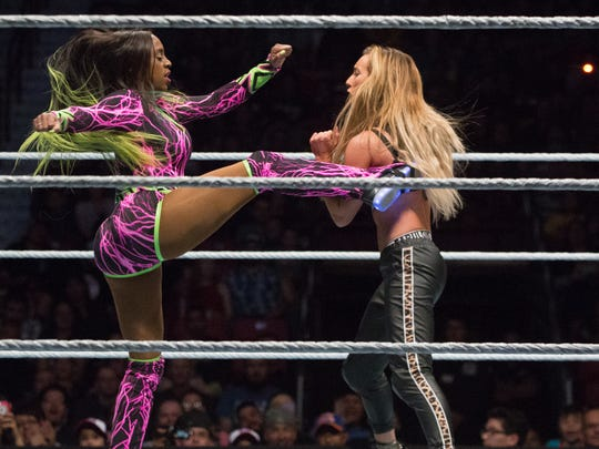 WWE wrestler Naomi kicks Carmella during a four wrestler match at WWE Smackdown Live, Saturday, February 11, 2017.