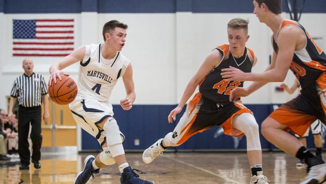 Marysville's Dylan Kiger fakes out Armada's Mitchell Ruczynski as he works the ball down court during a Class B district semifinal basketball game Wednesday, March 8, 2017 at Marysville High School.