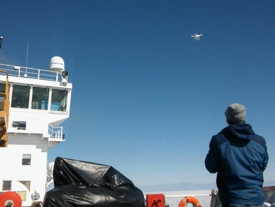 A NOAA researcher operates a quadcopter drone from