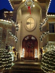 The home's dramatic front entrance is outlined by lights