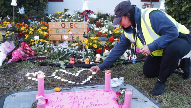 School crossing guard Wendy Behrend lights a candle at a memorial outside Marjory Stoneman Douglas High School during the one-year anniversary of the school shooting, Feb. 14, 2019, in Parkland, Fla. A year ago on Thursday, 14 students and three staff members were killed when a gunman opened fire at the high school.