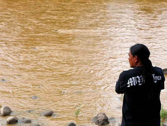 Travis Sells, of Farmington, stops to look at the orange plume flowing through the Animas River from the Gold King Mine spill on Saturday at Berg Park in Farmington.