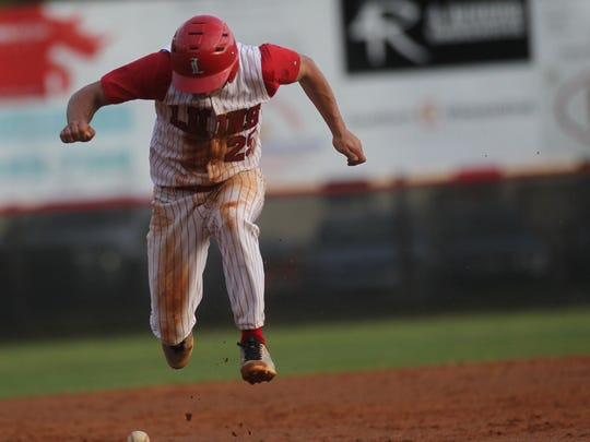 Leon's Tyler Borges jumps over a grounder hit at him while running from second to third base.