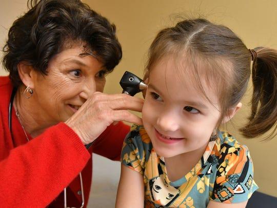 Dr. Jan Borowski checks out Harper Loiselle, 4, at