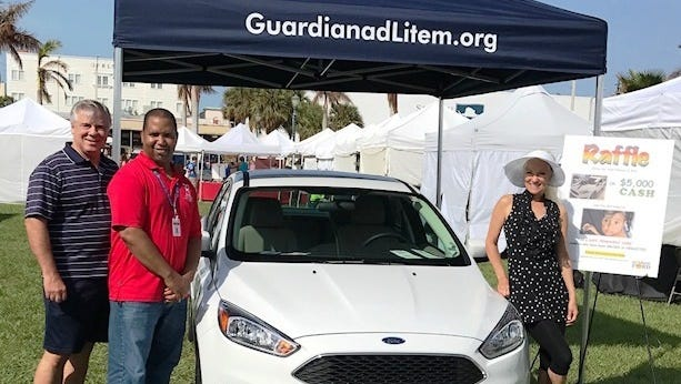 Bob Perry, president of Voices for Children, Omar Walker, Guardian ad Litem Volunteer Recruiter and Kip Lyman, event chair of The Ultimate Tailgate Party with the Ford Focus that will be raffled off at the Feb. 4 event, courtesy of Sunrise Ford.