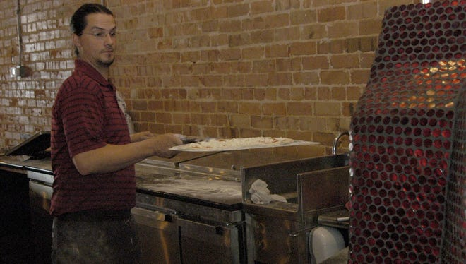 Zander's Woodfired Pizza General Manager Shaun Brinegar places a pizza in the restaurant's ruby red oven.