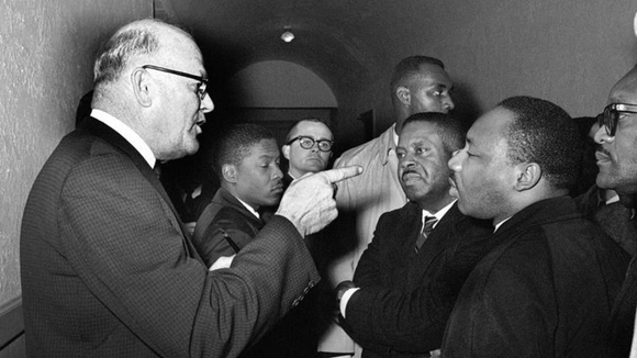 "Registrar Carl Golson shakes a finger at Martin Luther King Jr. during meeting at the courthouse in Hayneyville, Ala. on March 1, 1965. King inquired about voter registration procedures, but Golson told him that if he was not a prospective voter in Lowndes county, ""It's none of your business."" King visited two nearby counties after leading a voter registration drive in Selma."