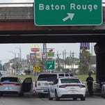 Baton Rouge Police block Airline Highway after police were shot in Baton Rouge, La., Sunday, July 17, 2016.  At least three officers are confirmed dead and at least three others wounded after the shooting, a sheriff's office spokeswoman said Sunday. One suspect is dead and law enforcement officials believe two others are still at large, the spokeswoman said.