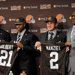 Cleveland Browns head coach Mike Pettine, left, helps cornerback Justin Gilbert display his jersey and general manager Ray Farmer, right, assists quarterback Johnny Manziel during a news conference at the NFL football team's facility in Berea.