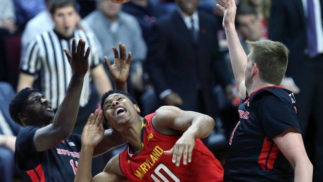 Maryland forward L.G. Gill (10) loses the ball as he is defended by Rutgers' C.J. Gettys, right, and Eugene Omoruyi, left.