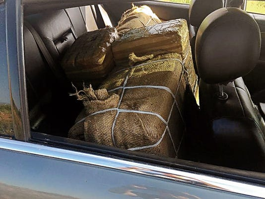 Courtesy Photo   Bundles of packaged marijuana can be seen in the back seat of an abandoned Jaguar sports car confiscated by U.S. Border Patrol agents.