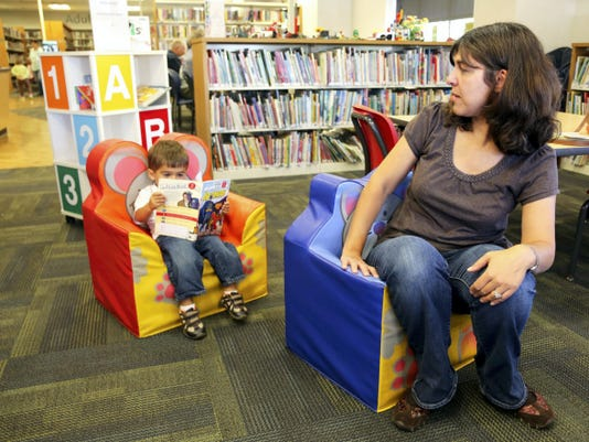 "Heather King of West Manchester Townships looks at her son Connor King, 2, as he reads a superhero book at the Dover Area Community Library on Sept. 23, 2014. Heather's favorite books as a kid were by Dr. Seuss and Connor likes to read them for now. ""He is starting to like Star Wars and superheroes like his older brother,"" she laughed, ""I never got into that as a kid, but I will adjust to his interests."""