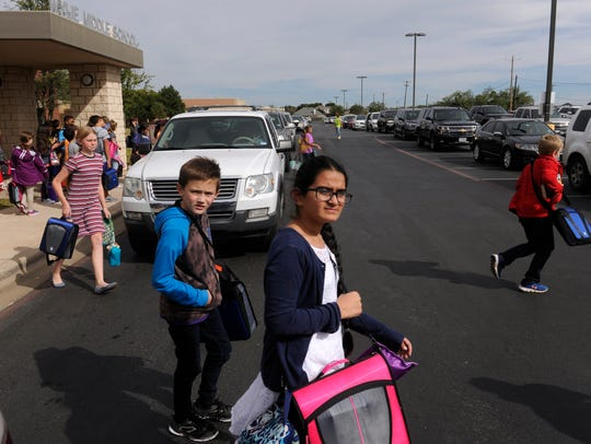 Children cross the crowded parking lot on the signal of Wylie Middle School principal Phil Boone after school Thursday. A bond before district residents could alleviate congestion around schools, as well as add new facilities.