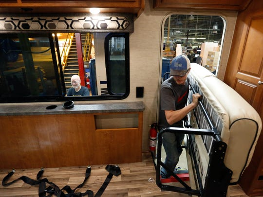 Isaac Haukoos of Kiester, Minn., brings in some seating to be installed Wednesday, Nov. 16, 2016, at the Winnebago manufacturing plant in Forest City, Iowa.