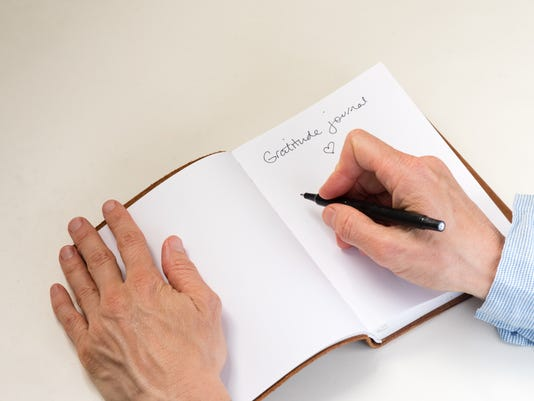 Woman's hands writing in gratitude journal