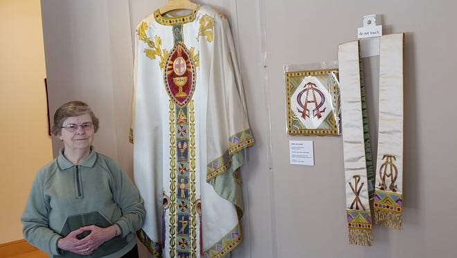 Sister Moira Wild, OSB, stands at the entrance to St. Benedict's Needlework Exhibit.