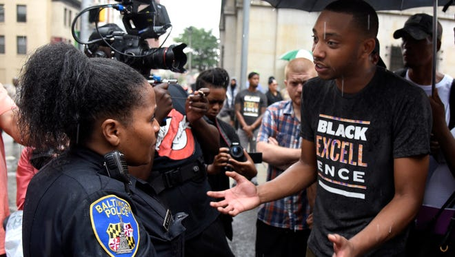 Baltiimore Police Sgt. K. Glanville talks with protesters outside the Baltimore Circuit Court on Sept. 10, 2015.