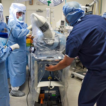 Dr. Joseph Nessler prepares a drill on a robotic arm May 21 as he gets ready to perform a total hip replacement at the St. Cloud Surgical Center. Nessler was using the new surgeon-controlled RIO robotic arm technology for precise alignment when placing implants.