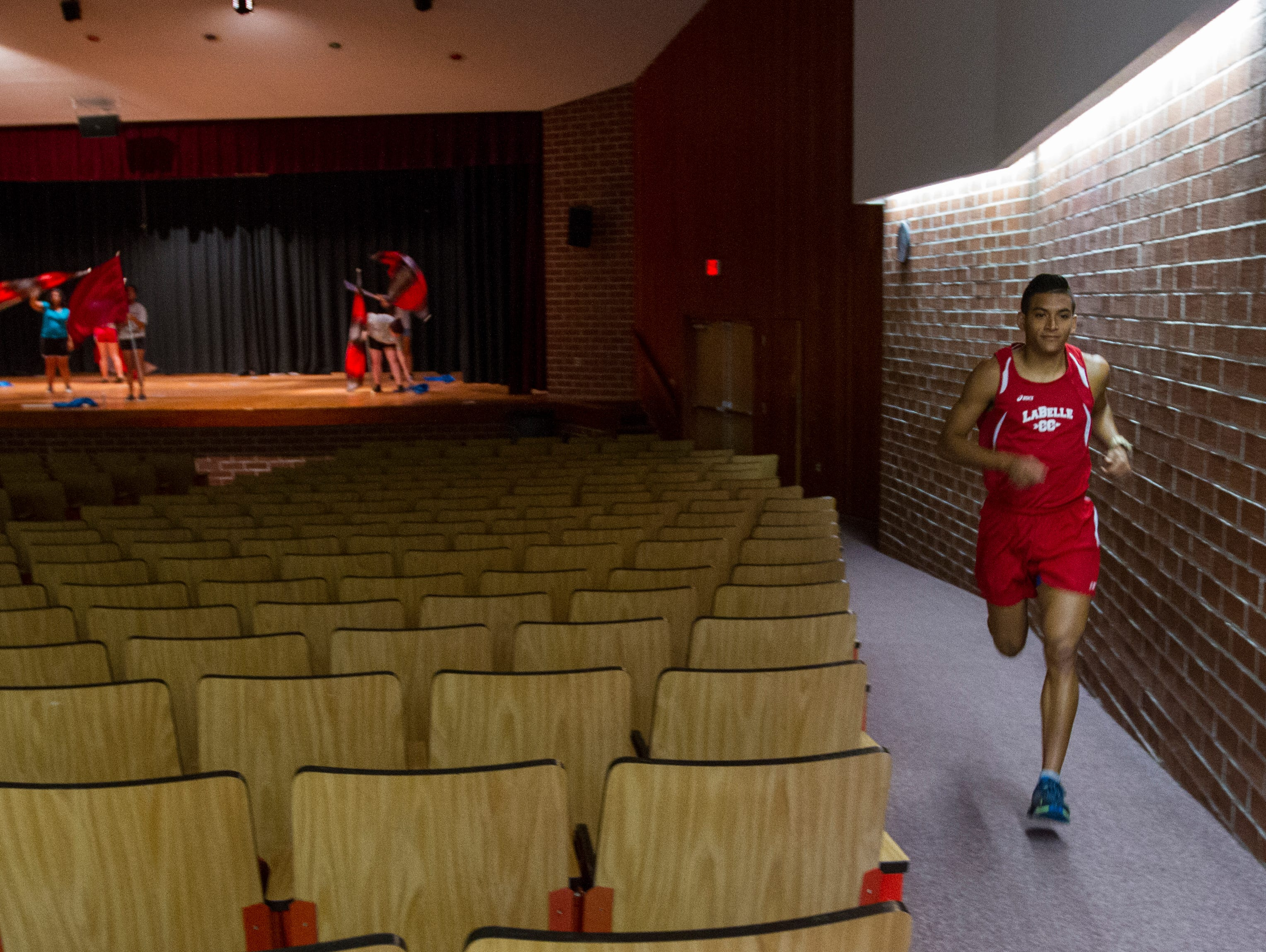 Cuban native Yoan Prado, 19, runs through his school's auditorium Tuesday afternoon, as students had to take shelter during a lighting storm warning. Prado, a cross country runner at LaBelle High School, is one of the best Cowboy runners and a top 10 state contender. He started at the Hendry county school two years ago.
