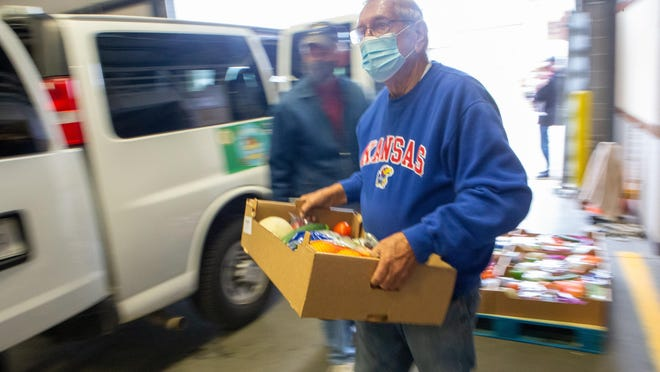 Norbert Kampsen, a volunteer for the Topeka Rescue Mission, helps loads a van full of food for Operation Food Secure at the mission's warehouse.