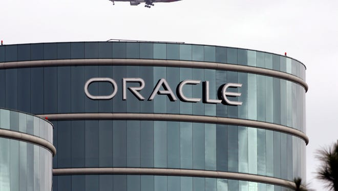 FILE - In this  Tuesday, March 20, 2012, file photo, a plane flies over Oracle headquarters in Redwood City, Calif. Oracle reports quarterly financial results after the market closes on Wednesday, Dec. 18, 2013. (AP Photo/Paul Sakuma, File) ORG XMIT: NYBZ143