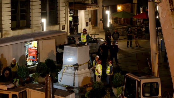Police and workers remove the John C. Breckinridge statue outside the former Fayette County Court House on October 17, 2017 in Lexington, Ky.