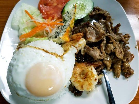 PHO 772's Rice Platter 772 includes grilled beef, pork, shrimp, shredded pork skins, and a pork sausage meatloaf served with jasmine rice topped with a fried egg and garnished with a mini salad.