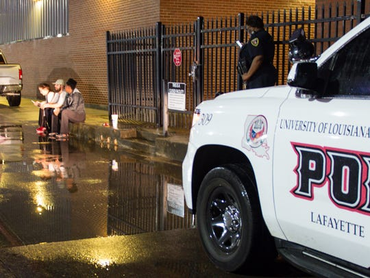 A UL police officer stands guard as Ragin Cajun softball players wait to get into their locked locker room.