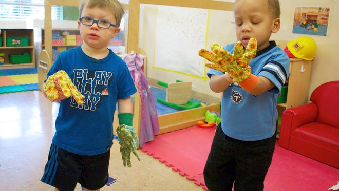 """A couple of """"the Green Room Guys"""" at the Ann Campbell Early Learning Center at MTSU don their gloves for a day of learning about plants and gardens."""