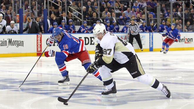 Pittsburgh Penguins center Sidney Crosby (87) skates in on a breakaway past New York Rangers defenseman Marc Staal (18) and scores a goal during the second period.