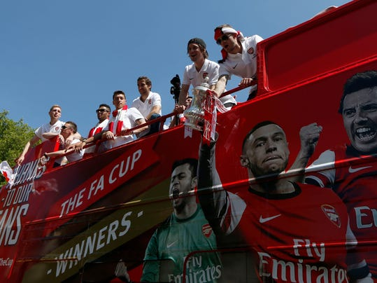 Arsenal's Jack Wilshere, right, and Tomas Rosicky, second right, show off the trophy to the supporters as the team parade through the streets of London Sunday May 18, 2014, aboard an open top bus in celebration of their English FA Cup win. Aaron Ramsey scored in extra time to clinch a 3-2 victory over Hull on Saturday, making Arsenal FA Cup Winners for the fifth time in Arsene Wenger's 14-year tenure as manager of 'The Gunners'.  (AP Photo/Sang Tan)