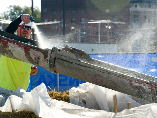 Phillip Schleeter, an employee with IMI Southwest, sprays down his concrete truck after working on the Multi-Institutional Academic Health Science & Research Center's footings Monday afternoon.
