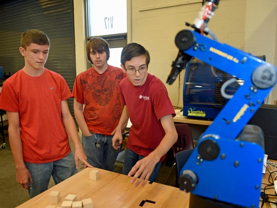 Students Connor Coyle, left, Alexander Harsh, both 16, and Jaren Bard, 17, program a Scrobot robot to do tasks in their pre-engineering class at Franklin County Career and Technology Center. Enrollment is increasing and more programs are being offered at the school.