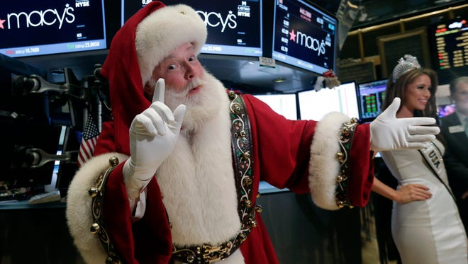 Santa Claus and Nia Sanchez, Miss USA 2014,  visit the trading floor after participating in opening bell ceremonies of the New York Stock Exchange Nov. 26.