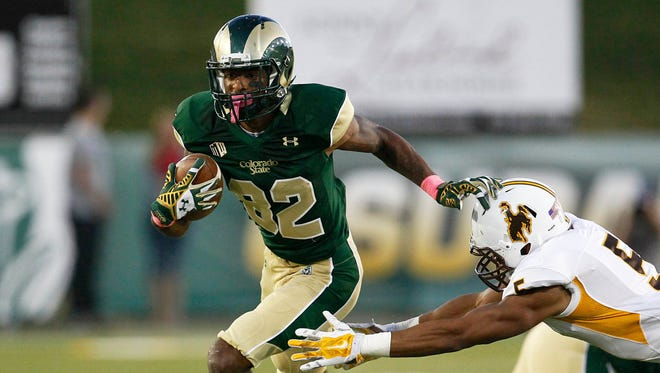 Colorado State Rams wide receiver Rashard Higgins (82) breaks the tackle of Wyoming Cowboys safety Jesse Sampson (5) in the second quarter at Hughes Stadium.